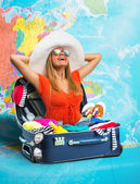 Young woman in suitcase on map — Stock Photo