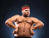 Fat man imitating muscular build — Stock Photo