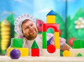 Man weared as baby play indoor — Stockfoto
