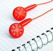 Röd hörlurar på anteckningsboken — Stockfoto