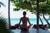 Woman silhouette in lotus pose — Stock Photo