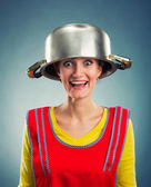 Happy housewife with sause pan on her head — Stok fotoğraf