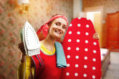 Ama de casa sonriente con tablas de planchar y plancha — Foto de Stock