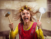 Crazy housewife with kitchen tools — Stock Photo