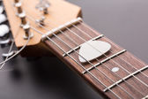 White pick in electric guitar strings — Stock fotografie