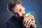Businessman holding rubik cube — Stock Photo