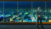 Businessman staying infront of city view — Stock Photo