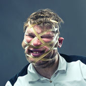 Freak man with rubber on his face — Stock Photo