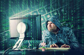 Hacker sitting at desk looking on computer screen — Foto Stock