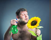 Portrait of man with sunflower, studio shoot — Foto Stock