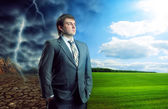 Businessman staying against bad and good weather — Stock Photo