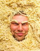 Man's face in pasta, closeup — Stock Photo