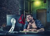 坐在办公桌前看电脑屏幕上的男人 — 图库照片