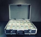Case full of money on gray background — Stock Photo