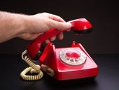 Red telephone handset in hand — Stock Photo