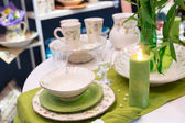 Served green table with glases and plates — Stock Photo