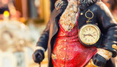 Ancient style clock on the statuette of man — Stock Photo