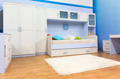 Bright bedroom with a bed and cupboard — Stock Photo