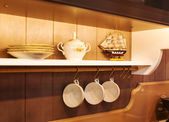 White plates and dinnerware in a cupboard — Stock Photo