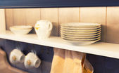White plates and dinnerware in a cupboard — Stok fotoğraf