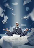 Businessman is meditating with documents — Stock fotografie