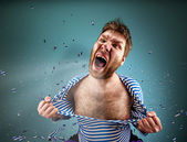 Man is tearing clothing on himself — Stock Photo