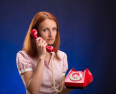 Redhead woman with red telephone — Stock Photo