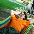 The young man has a rest in a hammock — Stock Photo #36727453