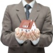 Businessman holding a toy house — Stock Photo