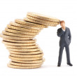 Figure of businessman and stack of coins — Stock Photo
