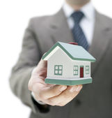 Real estate agent holding a toy house — Stock Photo