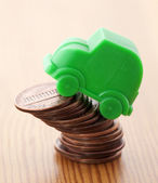 Green car miniature over pennies — Stock Photo