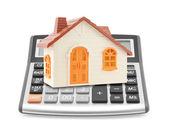 Small orange toy house on calculator — Stock Photo