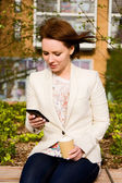 Casual business woman with coffee and phone — Stock Photo