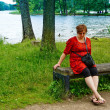 Middle-aged woman relaxing by the lake — Stockfoto