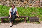 Middle-aged woman relaxing on a bench — Stock Photo