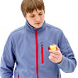 Portrait of a young guy in a jacket, eating apple — Stock Photo