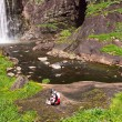 Cyclists resting near a waterfall — Stock Photo