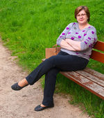 Middle-aged woman relaxing on a park bench — Fotografia Stock