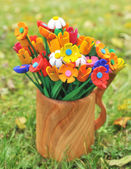 Bouquet multicolored artificial flowers in a vase — Stock Photo