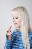 Woman holding a painkiller between finger — Stock Photo