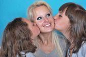 Una madre sonríe mientras recibe un beso en la mejilla de ella — Foto de Stock
