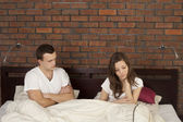 Upset young couple sitting seperately in bed — Stock Photo
