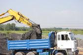Excavator and lorry — Stock Photo