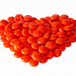 Stock Photo: Heart made from red pills isolated on white