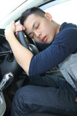 Tired young man asleep at the wheel — Stock Photo