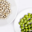Fresh and dried green peas on plate — Stock Photo