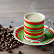 Coffee in striped cup with beans — Stok fotoğraf