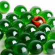 Group of green glass marbles with one orange — Stock Photo