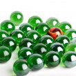 Group of green glass marbles with one orange - Stock Photo